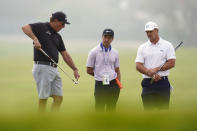 Phil Mickelson, left, talks with Bryson DeChambeau, right, and golf coach Chris Como, center, on the 12th hole during a practice round of the U.S. Open Golf Championship Monday, June 14, 2021, at Torrey Pines Golf Course in San Diego. (AP Photo/Gregory Bull)