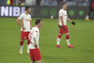 Leipzig players stand on the pitch in dejection after Dortmund's Erling Haaland scored his side's third goal during the German Bundesliga soccer match between RB Leipzig and Borussia Dortmund in Leipzig, Germany, Saturday, Jan. 9, 2021. (AP Photo/Michael Sohn)