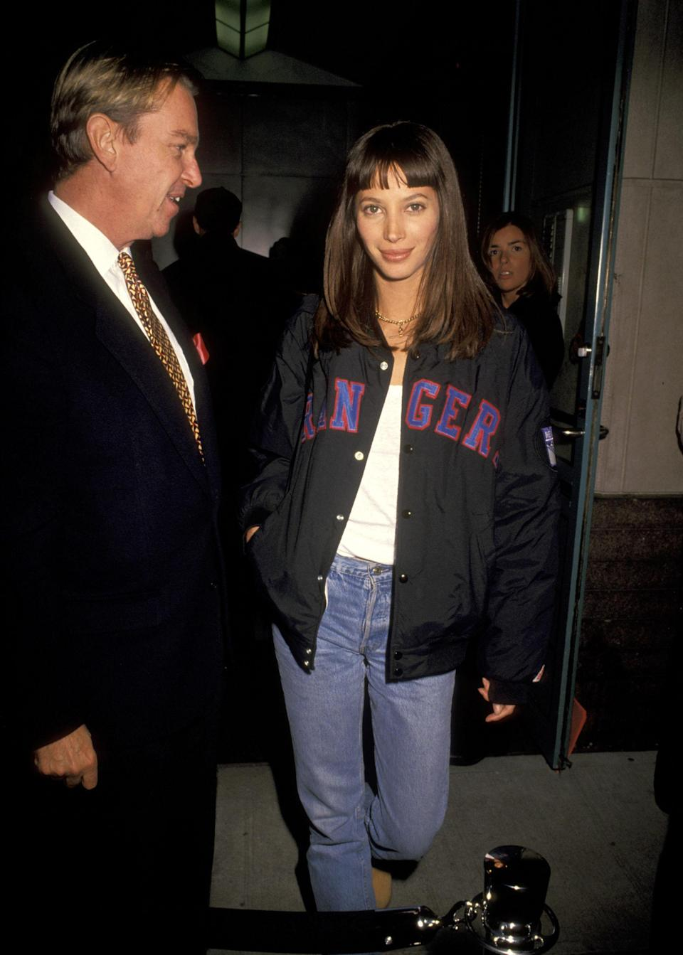 <p>Turlington attends a party for Grace Coddington wearing a baseball jacket and a blunt fringe, 1993</p>
