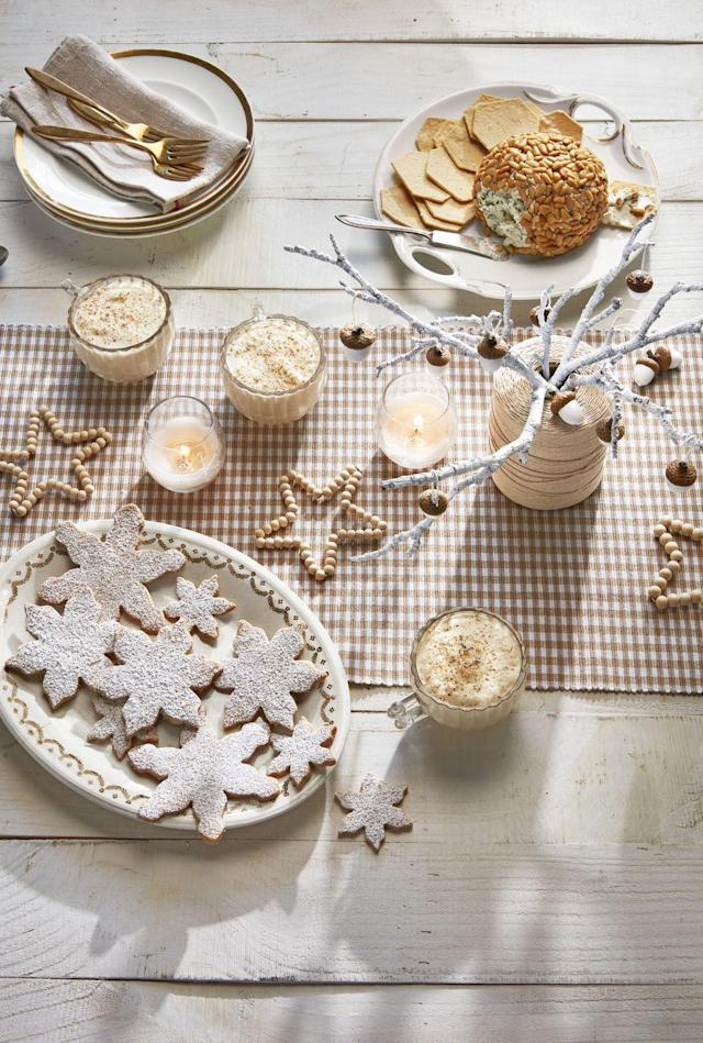 """<p>Textured neutrals and snowy motifs evoke a Scandinavian spirit on this dining table. To make the wooden bead stars, draw a five-point loop in one end of a piece of silver craft wire. Thread beads on wire, bending wire per drawing as you go. Feed loose end of wire through loop, crimp, and cut. As for the acorn tree centerpiece, paint nuts with white craft paint, leaving caps natural. Attach a loop of twine with hot glue. Hang from a spray-painted branch set inside a spool of twine. </p><p><a class=""""link rapid-noclick-resp"""" href=""""https://www.amazon.com/DICOBD-150pcs-Natural-Jewelry-Decoration/dp/B07S8TVCDG?tag=syn-yahoo-20&ascsubtag=%5Bartid%7C10050.g.644%5Bsrc%7Cyahoo-us"""" rel=""""nofollow noopener"""" target=""""_blank"""" data-ylk=""""slk:shop wooden beads"""">shop wooden beads</a></p>"""