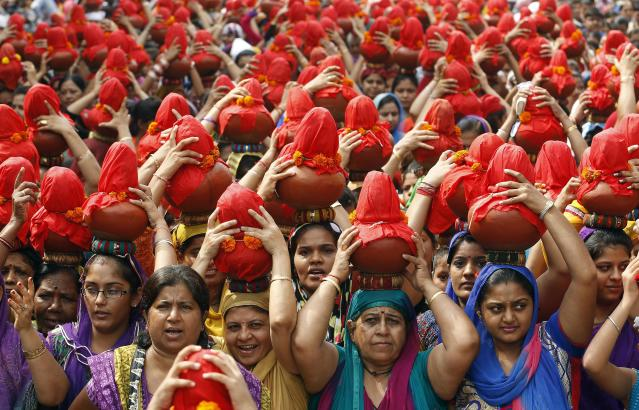 Women carry earthen water pots as they take part in a Jhulelal Chaliha procession in the western Indian city of Ahmedabad August 31, 2014. Jhulelal Chaliha, a 40-day-long fasting festival of the Sindhi community, ended on Sunday with a colourful procession of earthen pots carried by hundreds of male and female devotees on their heads for what they say to be the betterment of their family and society. REUTERS/Amit Dave (INDIA - Tags: RELIGION SOCIETY TPX IMAGES OF THE DAY)