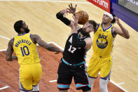 Memphis Grizzlies center Jonas Valanciunas (17) struggles for control of the ball with Golden State Warriors guards Damion Lee (1) and Brad Wanamaker (10) in the first half of an NBA basketball game Saturday, March 20, 2021, in Memphis, Tenn. (AP Photo/Brandon Dill)