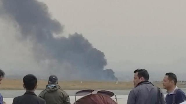 <p>People stand as smoke rises following the crash of a Bangladeshi aircraft at Kathmandu airport, Nepal March 12, 2018, in this picture grab obtained from social media video. (Photo: Nitin Keyal/via Reuters) </p>