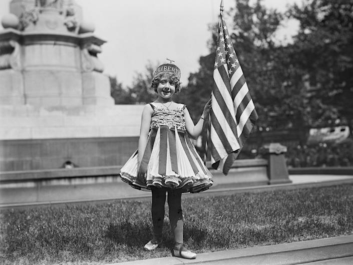A young girl holds up an American flag in Washington, DC, during the July 4th celebrations in 1916.