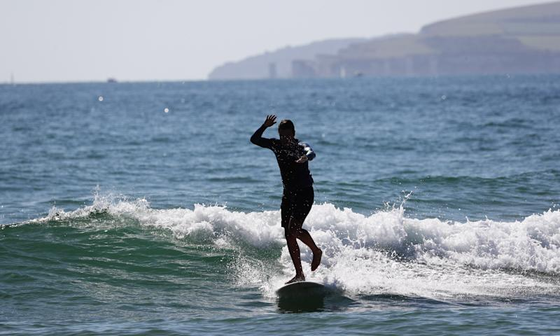 A surfer takes to the water at Bournemouth beach, as visitors have taken to the sand to make the most of the hot weekend weather across the UK.
