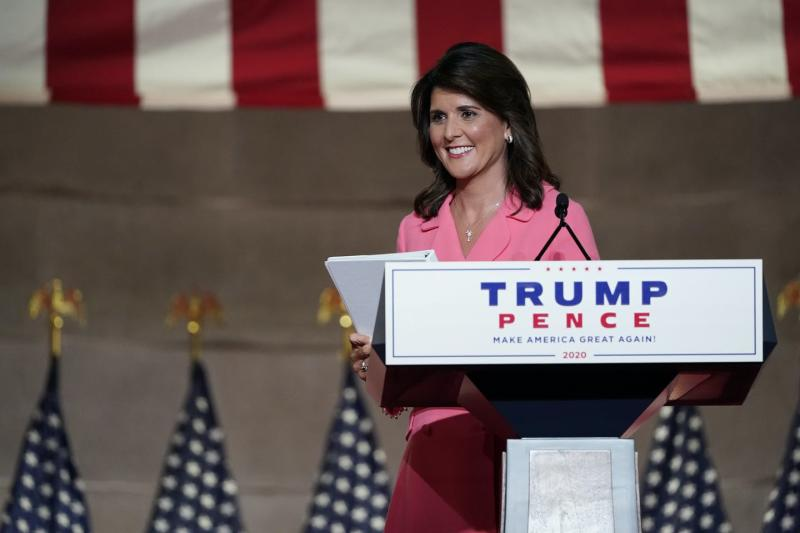 Nikki Haley, wearing a pink suit and carrying a document in her hand, smiles as she begins to walk away from a podium that reads Trump/Pence.