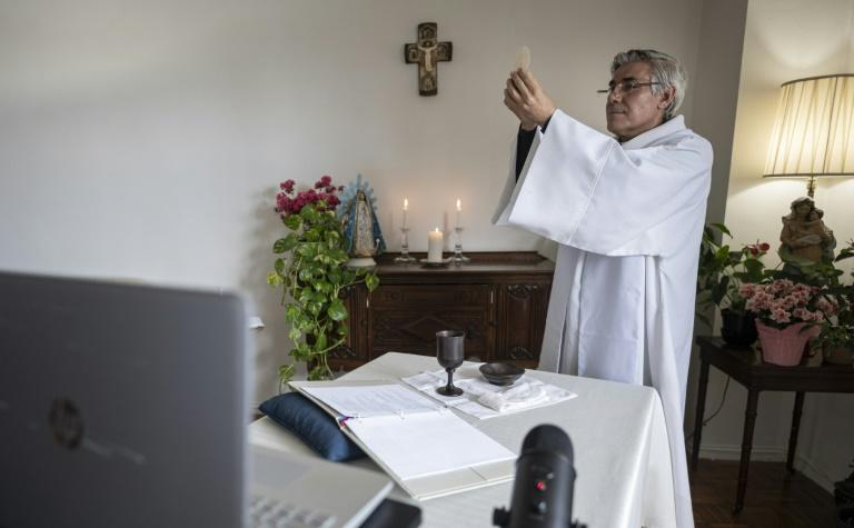 New York Lutheran priest Fabian Arias performs mass online from his home in the Bronx (AFP Photo/Johannes EISELE)