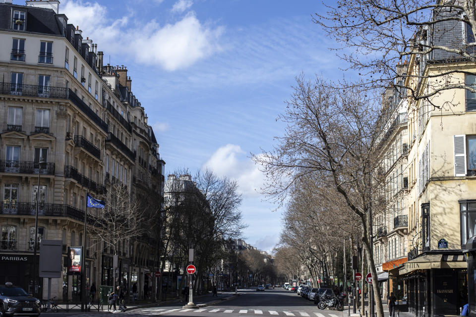 An empty street is pictured Sunday March 15, 2020 in Paris. For most people, the new coronavirus causes only mild or moderate symptoms. For some it can cause more severe illness. (AP Photo/Rafael Yaghobzadeh)
