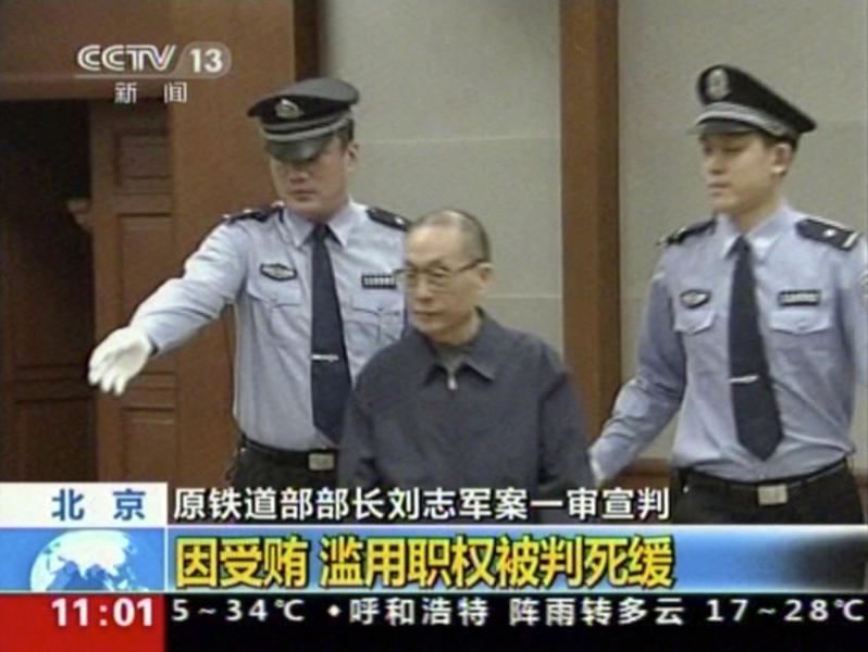 """In this image made from China Central Television video, former Chinese Railways Minister Liu Zhijun, center, is escorted into a courtroom at Beijing No. 2 Intermediate People's Court in Beijing Monday, July 8, 2013. The official Xinhua News Agency said Liu was sentenced to death with a two-year reprieve by a court in Beijing on Monday. Such sentences usually are commuted to life in prison with good behavior. Liu, 60, who oversaw the ministry's high-profile bullet train development, was accused of taking massive bribes and steering lucrative projects to associates. Chinese characters at bottom reads: """"Former Railway Minister Liu Zhijun sentencing,"""" """"Taking bribes and abuse of power sentenced to suspended death sentence."""" (AP Photo/CCTV via AP Video) CHINA OUT, TV OUT"""
