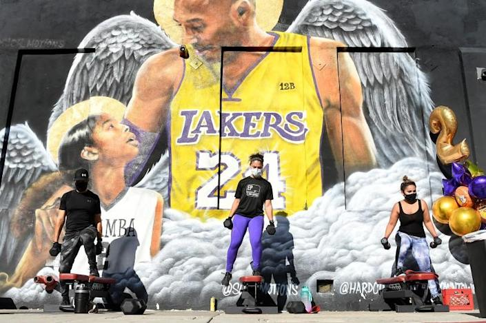 LOS ANGELES, CALIFORNIA JANUARY 26, 2021-People workout in front of a mural of Lakers legend Kobe Bryant and his daughter Gianna on the 1-year anniversary of their death outside of Hardcore Fitness Bootcamp in Downtown Los Angeles Tueswday. (Wally Skalij/Los Angeles Times)