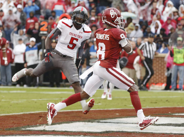 Oklahoma wide receiver Jalen Saunders (8) grabs a touchdown pass in front of Texas Tech defensive back Tre' Porter (5) during the second quarter of an NCAA college football game in Norman, Okla., Saturday, Oct. 26, 2013. (AP Photo/Sue Ogrocki)