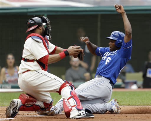 Kansas City Royals' Lorenzo Cain, right, scores ahead of the tag by Cleveland Indians catcher Carlos Santana in the second inning of a baseball game on Sunday, July 14, 2013, in Cleveland. Cain scored on a sacrifice fly by Alcides Escobar. (AP Photo/Tony Dejak)