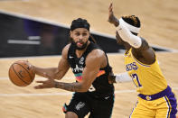 San Antonio Spurs' Patty Mills, left, drives against Los Angeles Lakers' Dennis Schroeder during the first half of an NBA basketball game Friday, Jan. 1, 2021, in San Antonio. (AP Photo/Darren Abate)