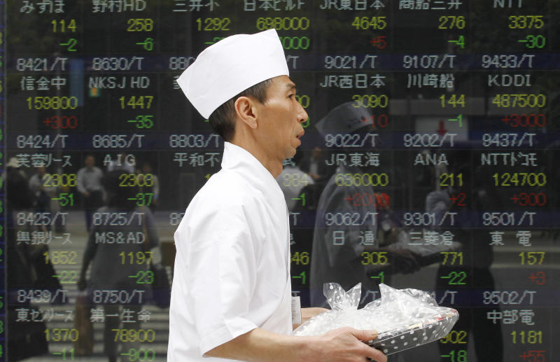 A Japanese chef carries a wrapped plate of sushi past the electronic stock board of a securities firm in Tokyo Thursday, May 31, 2012. Japan's Nikkei 225 index shed 158.62 points, or 1.84 percent, from Wednesday to end the morning session at 8,474.57. (AP Photo/Koji Sasahara)