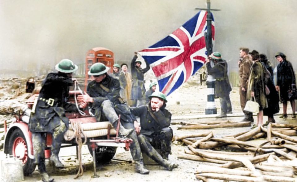<p>Firemen proudly hang a Union Jack on a lamp post after a two-night attack on Plymouth, Devon. </p>