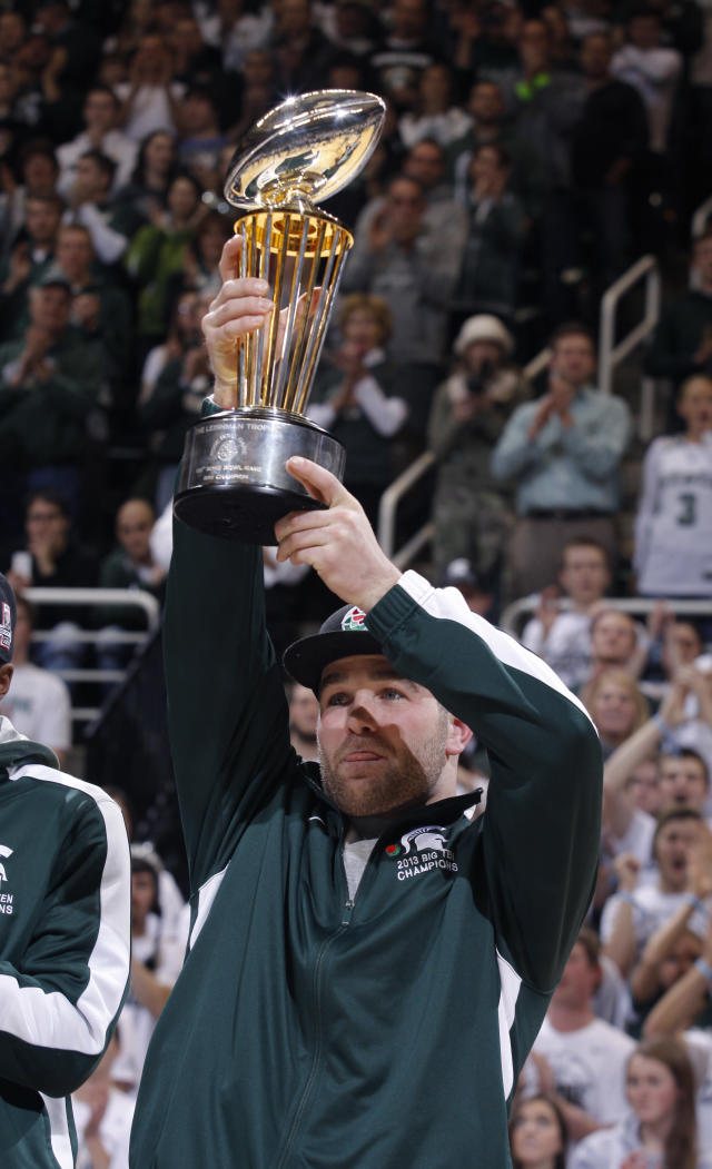 Michigan State football player Kyler Elsworth holds the 100th Rose Bowl championship trophy during halftime of an NCAA college basketball game between Michigan State and Ohio State, Tuesday, Jan. 7, 2014, in East Lansing, Mich. (AP Photo/Al Goldis)
