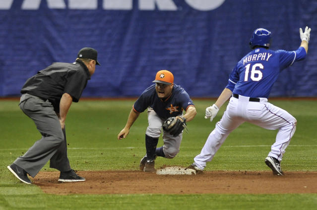 Texas Rangers' Donnie Murphy (16) gets safely to base against Houston Astros second baseman Jose Altuve, center, during a spring exhibition baseball game on Friday, March 28, 2014, in San Antonio. (AP Photo/Darren Abate)