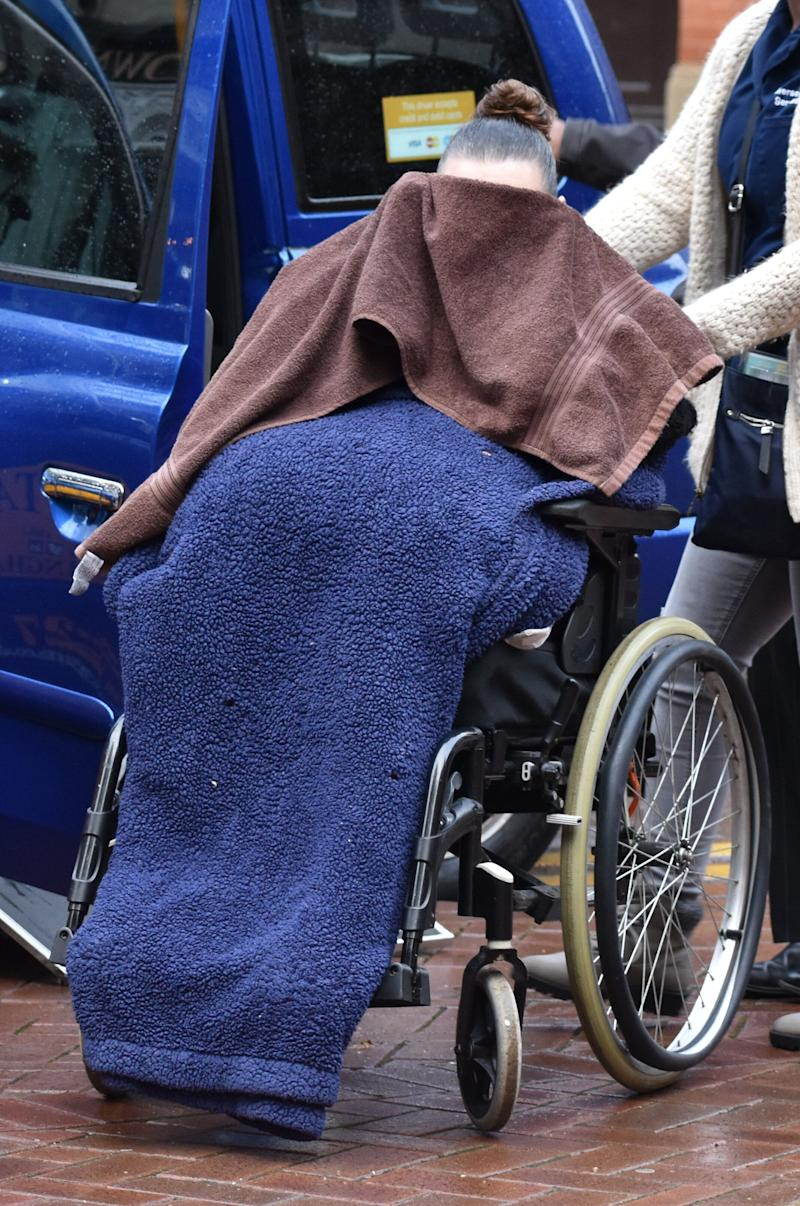 Kathleen Salmond covers her face with a towel as she arrives at Birmingham Crown Court (Photo: PA Wire/PA Images)