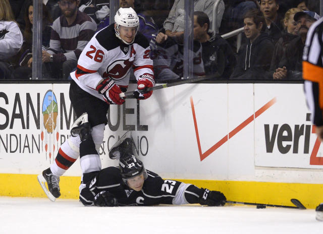Los Angeles Kings right wing Dustin Brown, right, dives for the puck as New Jersey Devils left wing Patrik Elias, of the Czech Republic, puts pressure on him during the second period of an NHL hockey game, Thursday, Nov. 21, 2013, in Los Angeles. (AP Photo/Mark J. Terrill)