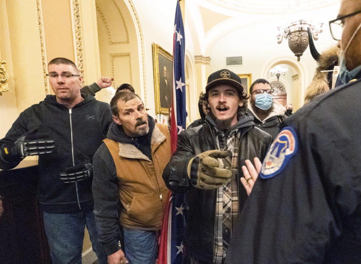 FILE - Violent protesters loyal to President Donald Trump, including Kevin Seefried, center, are confronted by U.S. Capitol Police officers outside the Senate Chamber inside the Capitol, Wednesday, Jan. 6, 2021 in Washington. Prosecutors say Seefried, photographed carrying a Confederate battle flag during a deadly riot in the U.S. Capitol was arrested Thursday, Jan. 14, after authorities used the image to help identify him. (AP Photo/Manuel Balce Ceneta)