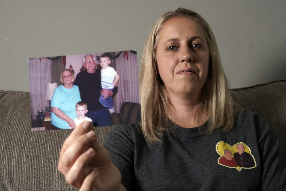 Kelly Brown holds up a December 2019 photograph of her parents John and Judy Trzebiatowski in her home Friday, June 25, 2021, in Menomonee Falls, Wis. Both of Brown's parents died from COVID-19. (AP Photo/Morry Gash)