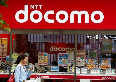 A woman walks past a brach of Japanese mobile communications company NTT Docomo in Tokyo