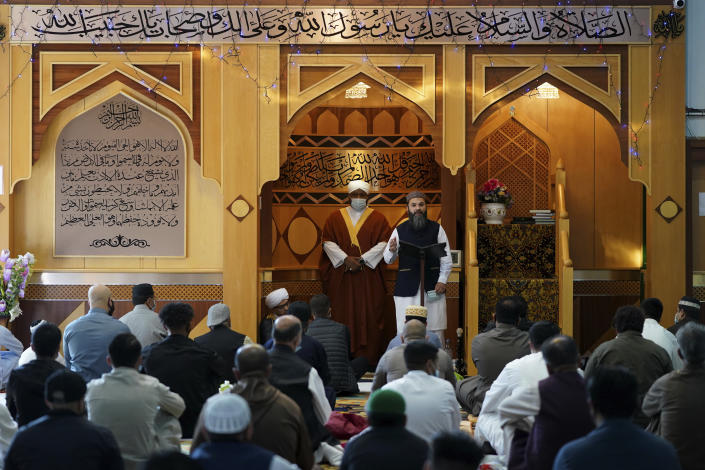 Hammad Khan, top right, the Chair of the Executive Committee at Manchester Central Mosque addresses the congregants partly about the new coronavirus safety measures, in Manchester, northern England, after having their temperatures checked at the entrance to try stop the spread of coronavirus, as Muslims worldwide mark the start of the Eid al-Adha holiday, Friday, July 31, 2020. The British government on Thursday night announced new rules on gatherings in some parts of Northern England, including Manchester, that people there should not mix with other households in private homes or gardens in response to an increase trend in the number of cases of coronavirus cases per 100,000 people. (AP Photo/Jon Super)
