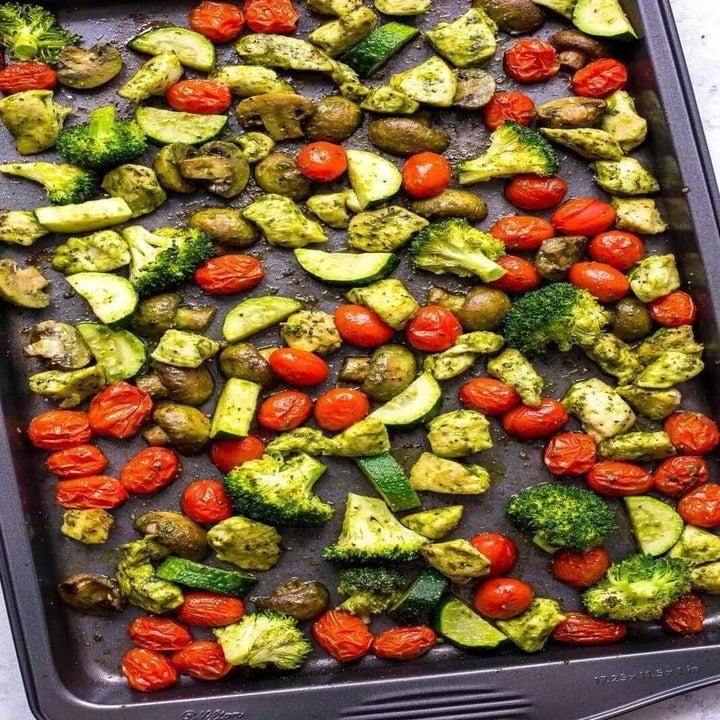 Pesto chicken, broccoli, and tomatoes on a sheet pan.