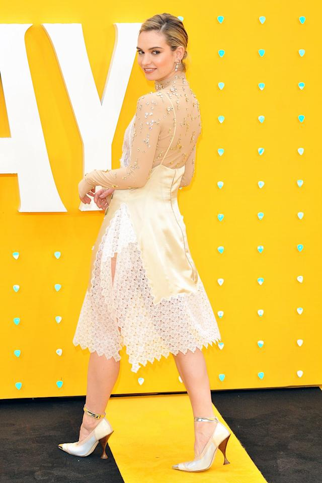 in a V-neck lace dress with sheer neckline and sleeves covered in jeweled appliqués at the premiere of <em>Yesterday</em> in London.