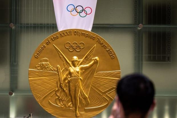 A man takes pictures of a large-scale reproduction of the Tokyo 2020 Olympic Games gold medal.  (Philip Fong/Getty Images - image credit)