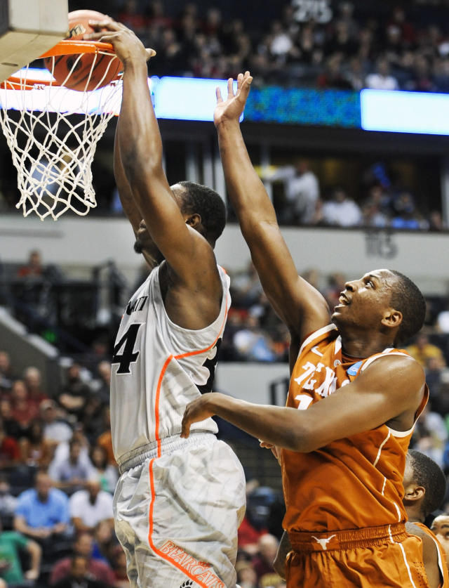 Cincinnati forward Yancy Gates, left, dunks the ball ahead of Texas forward Jonathan Holmes, right, in the first half of a second-round NCAA college basketball tournament game on Friday, March 16, 2012, in Nashville, Tenn. (AP Photo/Donn Jones)