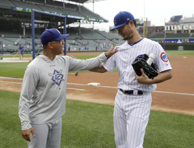Los Angeles Dodgers manager Dave Roberts, left, talks with former player Chicago Cubs starting pitcher Yu Darvish, after Darvish pitched a simulated game before a baseball game between the two clubs Wednesday, June 20, 2018, in Chicago. (AP Photo/Charles Rex Arbogast)