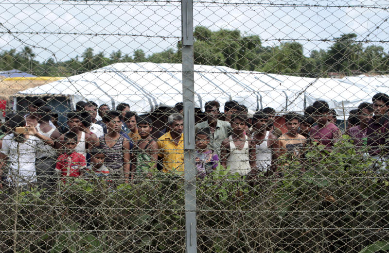 FILE - In this June 29, 2018, file photo, Rohingya refugees gather near a fence during a government organized media tour to a no-man's land between Myanmar and Bangladesh, near Taungpyolatyar village, Maung Daw, northern Rakhine State, Myanmar. A government security operation in Myanmar's Rakhine state sparked a humanitarian crisis that sent hundreds of thousands fleeing to neighboring Bangladesh. (AP Photo/Min Kyi Thein, File)