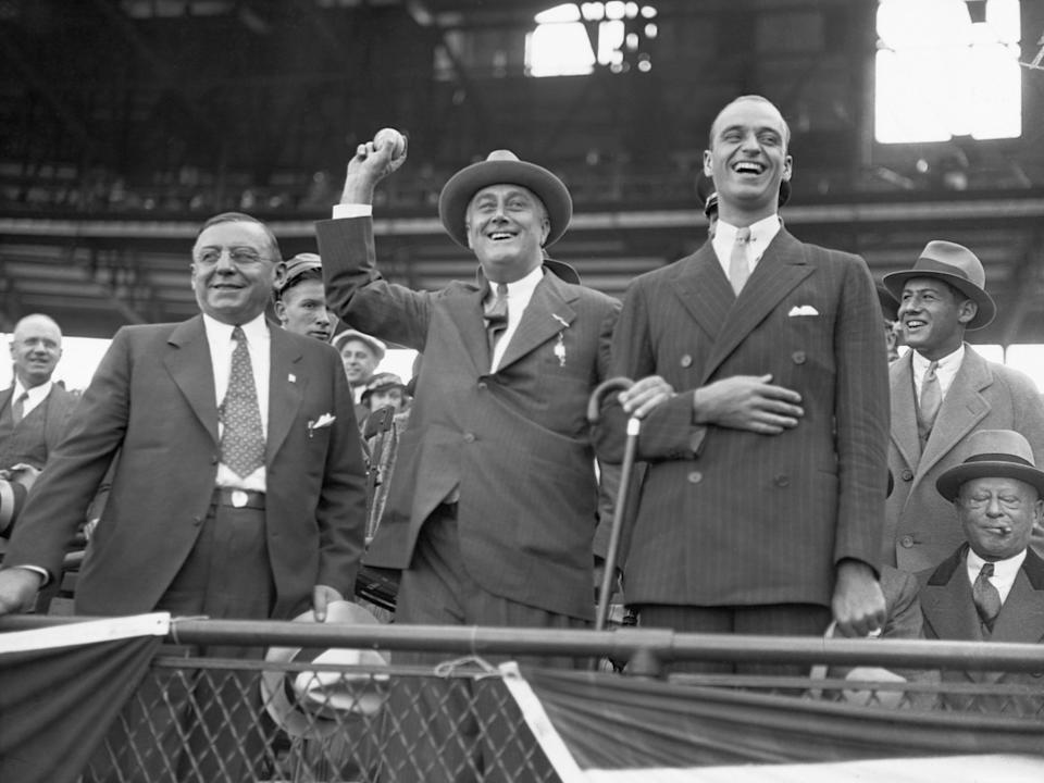 New York Governor and presidential candidate Franklin Roosevelt throws out a baseball at the last game of the 1932 World Series between the Chicago Cubs and the New York Yankees. To the right is his son James. To the left is Chicago Mayor Anton Cermak.