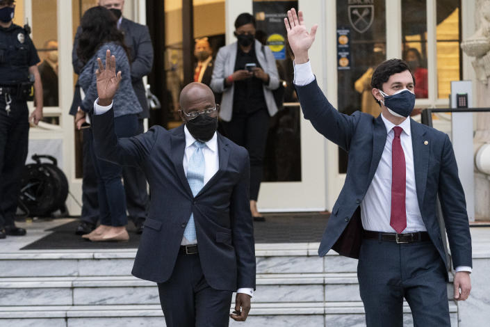 Sen. Raphael Warnock, D-Ga., Sen. Jon Ossoff, D-Ga., wave to the crowd after speaking with President Joe Biden and Vice President Kamala Harris during an event at Emory University, Friday, March 19, 2021, in Atlanta. (AP Photo/Alex Brandon)
