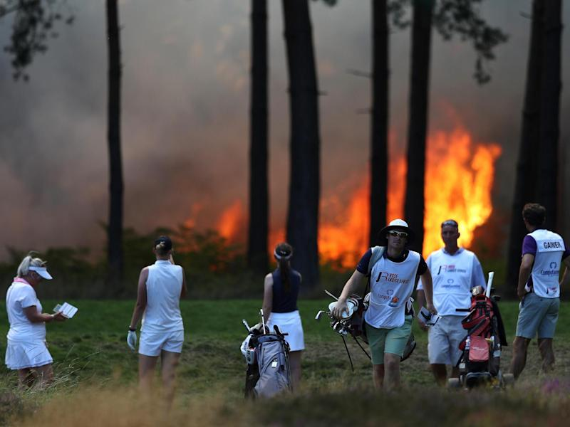 Players Sophie Powell, Cara Gainer and Gabriella Cowley and their caddies look on as a fire nears the 10th hole: Getty Images