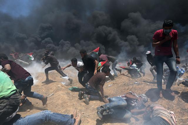 <p>Palestinian demonstrators run for cover from Israeli fire and tear gas during a protestat the Israel-Gaza border in the southern Gaza Strip against the U.S. Embassy's move to Jerusalem, on May 14, 2018. (Photo: Ibraheem Abu Mustafa/Reuters) </p>