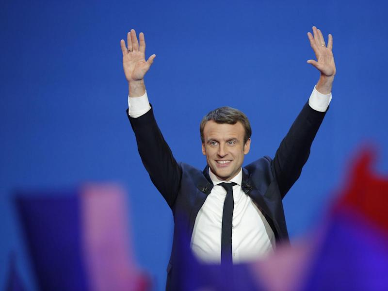 Emmanuel Macron takes to the stage after the first results of the election were announced (AP)