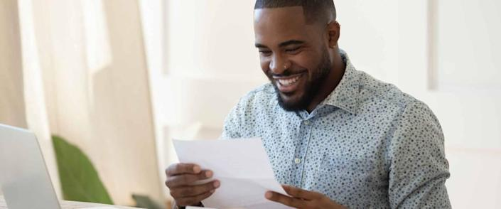 Smiling african American man sit at desk working at laptop reading good news in postal correspondence. He just got an unexpected tax refund.