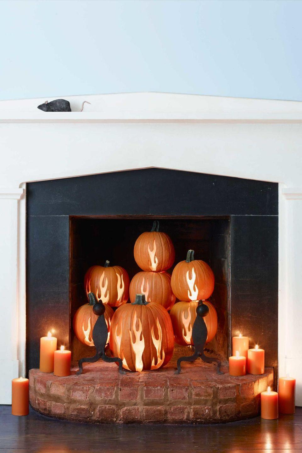 <p>Set the scene with a whole pumpkin tableau. Avoid any <em>real </em>fires by opting for flameless illumination instead. </p>