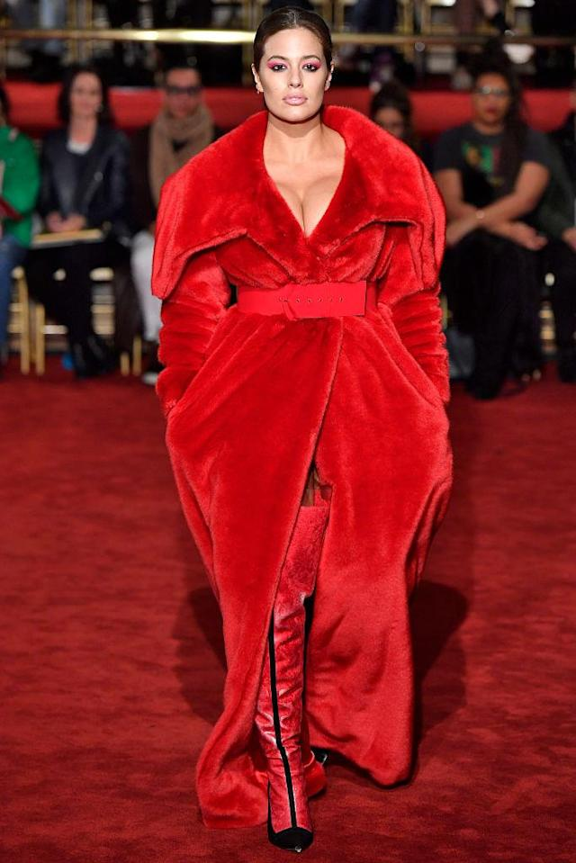 <p>For her first walk down the runway of the season, the model wore a belted fluffy red coat, with nothing but thigh-high boots underneath. (Photo: Getty Images) </p>