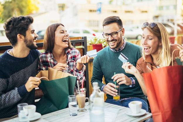 Group of happy friends at a cafe holding their credit cards