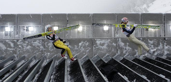 Simon Ammann of Switzerland and Austria's Martin Koch (R) walk down the stairs for their practice jump on the Large Hill HS134 at the Nordic Ski World Championships in Oslo, March 1, 2011.
