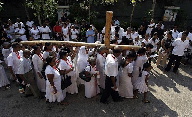 Catholics carry a holy cross at a street parade during a special Good Friday mass in Colombo, Sri Lanka. Holy Week is celebrated in many Christian traditions during the week before Easter.