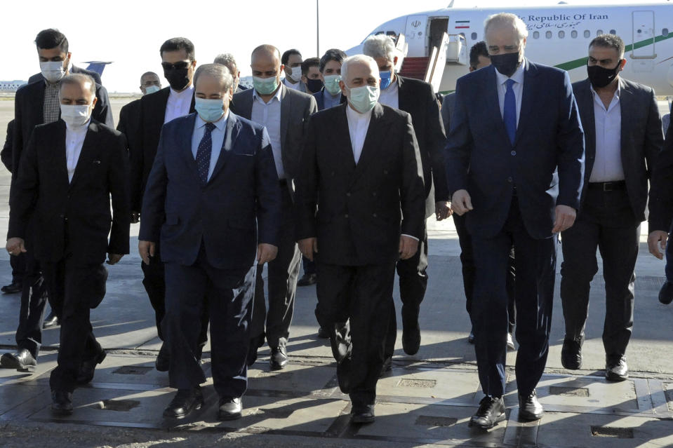 In this photo released by the Syrian official news agency SANA, Syria's Foreign Minister Faisal Mekdad, second left front, receives his Iranian counterpart Mohammad Javad Zarif, center, on his arrival to the airport, in Damascus, Syria, Wednesday, May 12, 2021. Zarif said his country is ready for closer ties with its regional rival Saudi Arabia, saying Wednesday he hoped recent talks would lead to greater stability in the region. (SANA via AP)