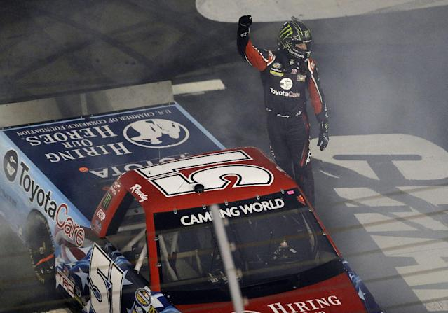 Kyle Busch celebrates following his victory in the NASCAR Truck series auto race in Concord, N.C., Friday, May 16, 2014. (AP Photo/Gerry Broome)
