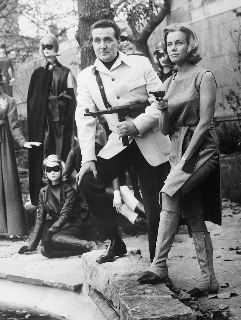 """(Original Caption) 11/8/1963-London, England- Looking very dangerous as leaders of a masked gang, Honor Blackman and Patrick MacNee stand well armored. Actually, the couple star in the British adventure TV series, """"The Avengers,"""" and are demonstrating why their fashions were inspired by the characters they portray. Their ensembles were designed by Frederick Starke and Hardy Amies."""