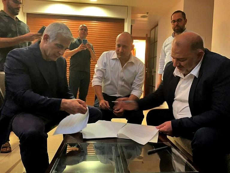 Mansour Abbas (R), leader of the Islamic conservative party Raam, signs the coalition agreement