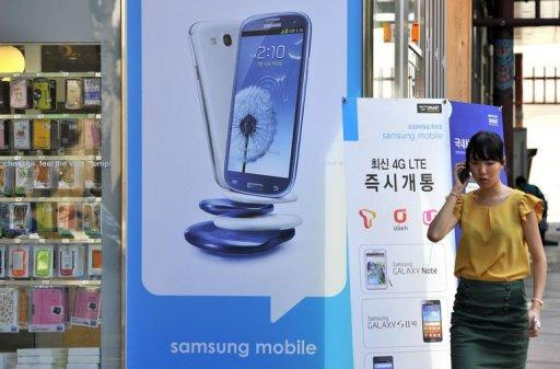 A woman walks past a signboard (C) of Samsung Galaxy S3 at a mobile phone shop in Seoul on August 27, 2012. Samsung sought Monday to rally employees after a $1.05 billion US court judgment in favour of arch-rival Apple pushed its shares sharply lower amid fears about the fallout in the key American market