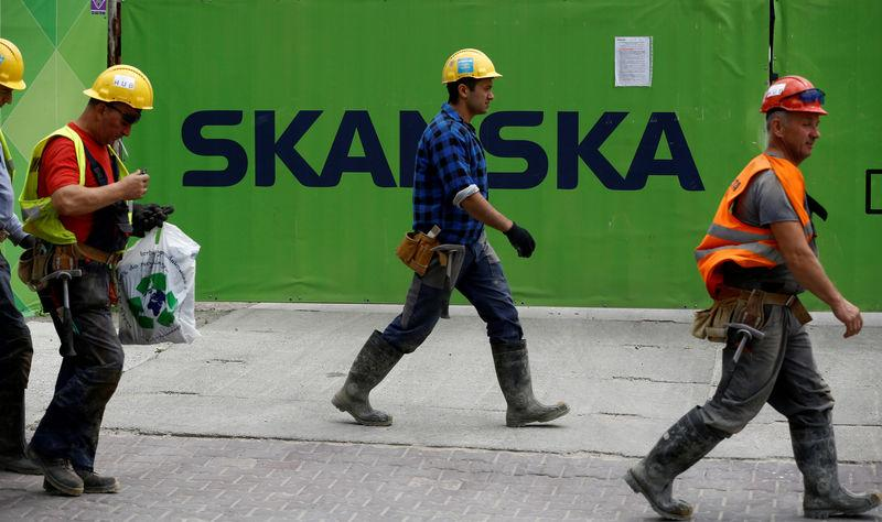 FILE PHOTO: Workers walk past a Skanska logo seen on a fence at a construction site In Warsaw, Poland June 1, 2017. REUTERS/Kacper Pempel/File Photo